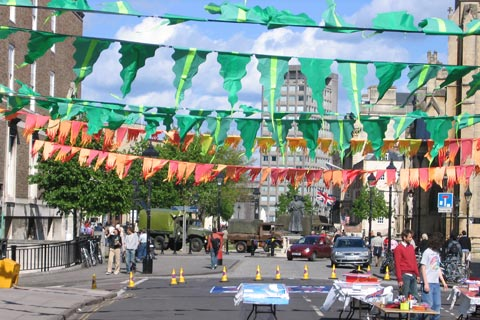 View of a street criss-crossed with hand made triangular bunting