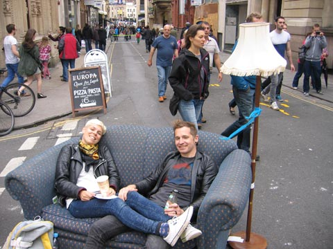 A young couple on a sofa in the street