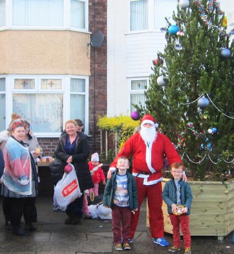 A resident dressed as Father Christmas with smiling neighbours in the street