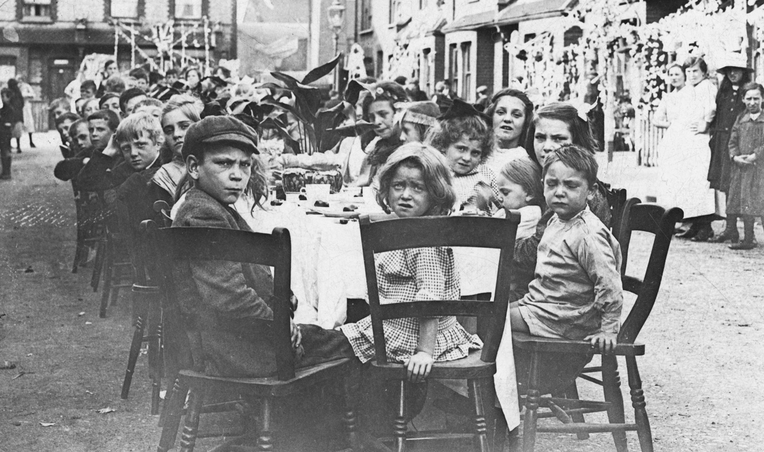 A black and white photo of young children seated around a table in a street during a Peace Tea in 1919