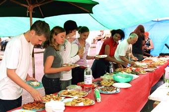 People selecting food from a street party buffet