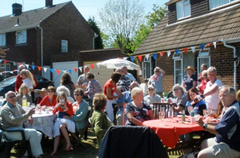 Groups of neighbours sitting around tables in a garden on a sunny day