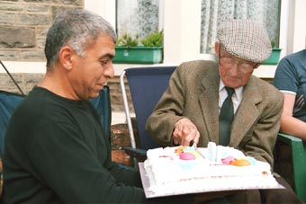 A older resident cutting his birthday cake