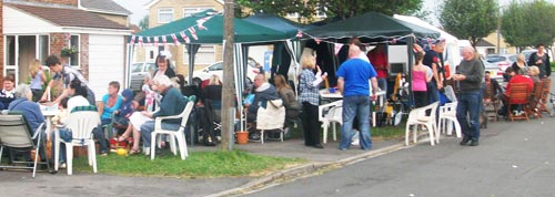 Neighbours gathered in a driveway under gazebos and bunting