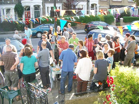 Residents standing and sharing food and drinks on the pavement with bunting hanging above
