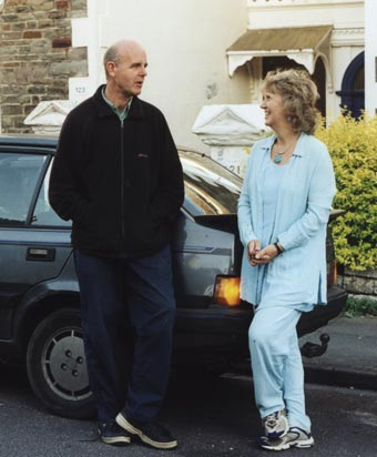 Man and woman chatting next to a parked car