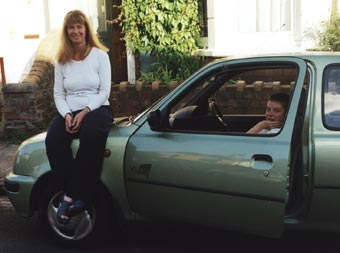 A smiling mother sits on the car bonnet with her son in the driver's seat